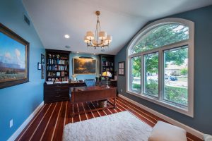 Home office with blue walls and large rounded window and hardwood floors