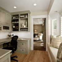 Home office with wrap around desk and a bay window with a cushioned window seat | Renovation Design Group