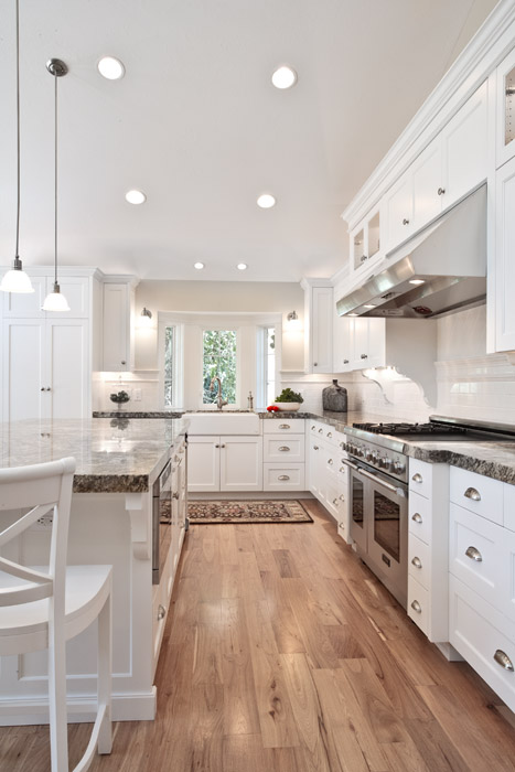 Large Kitchen with white cabinets and hardwood floors and farm sink | Renovation Design Group