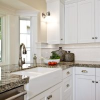 White farm sink and white cabinets in kitchen | Renovation Design Group