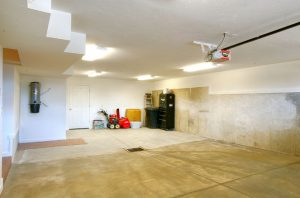 large garage with storage space and drain | Renovation Design Group