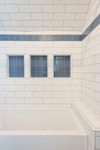 After_Interior_Family Bathroom_Bathtubs, white tile, blue accent tiles, large bath tub, smokey windows   Renovation Design Group