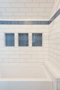 After_Interior_Family Bathroom_Bathtubs, white tile, blue accent tiles, large bath tub, smokey windows | Renovation Design Group